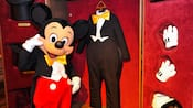 Mickey Mouse standing in front of a wardrobe closet filled with clothes, including his tuxedo and white gloves