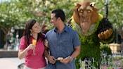Una pareja sonríe mirándose uno a otro cerca de una exhibición de arbustos inspirada en Beauty and the Beast de Disney