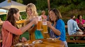 Three women stand around an outside table and toast glass steins filled with beer