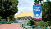 A sign outside a domed pavilion reads Celebrating 20 Years, Epcot International Food and Wine Festival, Festival Center, Open Daily, 9 A.M. to Park Close