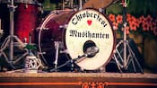 An Oktoberfest-themed bass drum placed on the center of the stage amid a multi-piece drum kit