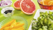 A variety of ingredients arranged on a table for the Mix It, Make It, Celebrate It! hands on workshop including a sliced grapefruit, a bowl of sliced red onion and bowls of mango spears, orange slices and greens