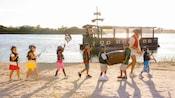 Uma mulher e 7 crianças vestidas de pirata andam em uma praia