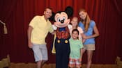 A mom, daughter, dad and son smile while posing with a magician-themed Mickey at Magic Kingdom park
