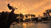 Estatua de Mickey el brujo parado sobre la Piscina Fantasía en Disney's All-Star Movies Resort al atardecer