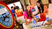 Une jeune famille est ravie de trouver les cadeaux et les surprises Disney qui les attendent dans leur chambre d'hôtel