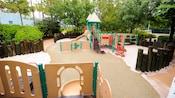 Um playground de areia com aparato para escaladas, escorregadores, redes e trepa-trepa