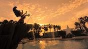 Silhueta contra o pôr do sol da Sorcerer Mickey Fountain na Fantasia Pool no Disney's All-Star Movies Resort