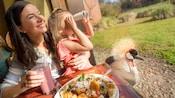 Una familia sonriente comiendo en una mesa de un restaurante mientras la hija juega con un par de binoculares