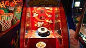 A popcorn game flanked by basketball and baseball games in a Disney hotel arcade