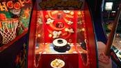 Un jeu de maïs soufflé entre des jeux de basketball et de baseball dans la salle d'arcade d'un hôtel Disney