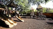 A gravel playground with slides and platforms under thatched roofs at Disney's Animal Kingdom Lodge