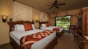2 queen beds with curtained headboards, TV in carved wood chest, wall sconces, ceiling fan, balcony