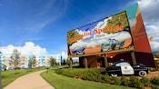 """Um carro de xerife sob um outdoor com os dizeres """"Radiator Springs, a Happy Place"""""""