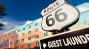"""Uma placa de """"Guest Laundry"""" abaixo de uma placa estilo brasão com os dizeres """"Route 66"""""""