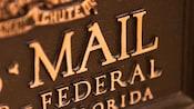 Close-up da frente de uma canaleta de bronze do U.S. Mail