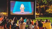 Guests sit on grass and watch Beauty and the Beast at night