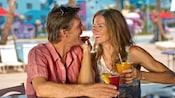 Un couple souriant tient des boissons près d'une piscine
