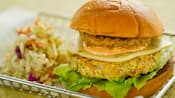 A veggie burger with cheese, a veggie patty, lettuce, sauce, and an onion ring next to a pile of coleslaw