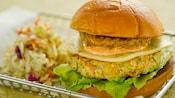 Una hamburguesa vegetariana con queso, lechuga, salsa y un onion ring junto a una pila de ensalada de col