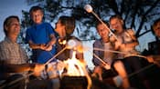 Una familia tostando malvaviscos en una fogata