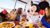 Família saboreia a refeição em uma mesa de café da manhã enquanto o Mickey Mouse conversa com uma menina