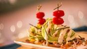 2 trozos de lechuga repollada, adornada con cebollines, aderezo ranch, trocitos de tocineta y tomates cherry