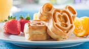 A breakfast order of Mickey waffles, whole strawberries and juicy orange slices