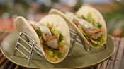 A duo of tacos in flour tortillas with lettuce, carrots, cilantro and freshly grilled pieces of fish