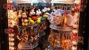 Assortiment de porte-clés à peluches, de Mickey Mouse à Winnie l'ourson, sur un présentoir