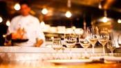Varios vasos de vino sobre una barra, con una cocina de exhibición en el fondo
