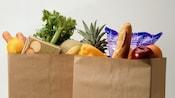 2bolsas de compras de papel, repletas de productos como pan, frutas y vegetales