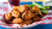 A pile of buffalo wings on a plate with celery sticks
