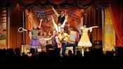 Un grupo de actores con atuendos de pioneros posan en un escenario con un cartel que dice Pioneer Hall Players