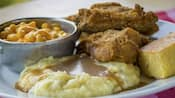 Fried chicken, cornbread, mac and cheese and mashed potatoes covered in gravy on a plate