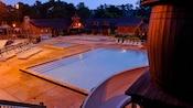 Visão parcial de um barril e tobogã aquático na Meadow Swimmin' Pool próximo a piscina infantil à noite