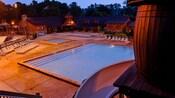 Vista parcial de un barril y un tobogán acuático en Meadow Swimmin' Pool junto a una pileta para niños pequeños en la noche