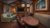 Mesa de jantar rústica em frente a uma poltrona, um sofá com almofadas e uma TV de tela plana.