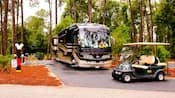 Una lujosa caravana y un carrito de golf brindan comodidad en los alrededores de los sitios para acampar