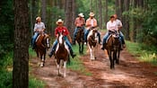 Cinq visiteurs et une cowgirl membre de l'équipe à cheval, sur un chemin dans les bois
