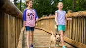 Two girls walk a small dog on a leash across a wooden bridge