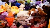 Close-up de uma variedade de prêmios de brinquedos de pelúcia no fliperama de um hotel Disney