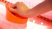 Close-up da mão de uma pessoa segurando um disco de hóquei de mesa laranja em uma mesa de jogos