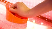 Close-up of a person's hand holding an orange air hockey paddle on the surface of the game table