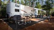 Acampamento com um trailer estacionado na área pavimentada com churrasqueira e mesa para piquenique