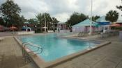 Una piscina con muebles para terraza y un hotel de baja altura en el fondo