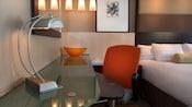 Un escritorio de vidrio con lámpara y silla de oficina junto a una cama en Disney's Contemporary Resort