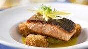 Un filet de saumon reposant sur des beignets de crabe et garni de gingembre tranché