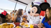 A family eats at a table plated with breakfast food while Mickey Mouse talks to a little girl