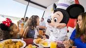 Une famille mange à une table garnie de mets de déjeuner alors que Mickey Mouse parle à une petite fille